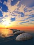 Roche dans l'eau et le coucher du soleil jaune Photo libre de droits