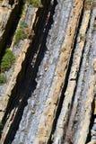 Roche de flysch sur le bord de la mer dans l'eau Photographie stock