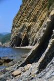 Roche de flysch sur le bord de la mer dans l'eau Photos stock