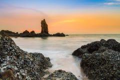 Roche de mer au-dessus de littoral avec le beau ciel de coucher du soleil Photos libres de droits