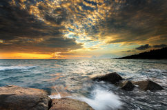 Roche de vague de coucher du soleil sur la plage Image stock