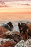 Roche, eau et coucher du soleil Photographie stock libre de droits