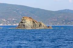 Roche en mer bleue Photographie stock