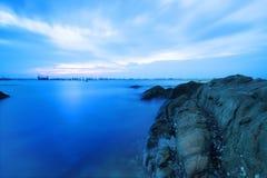 Roche en mer de coucher du soleil Photographie stock libre de droits