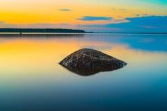 Roche en pierre dans la longue photographie d'exposition de lac photo libre de droits