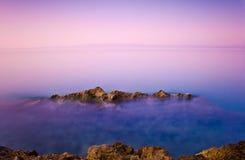 Roche en planche et un bel océan au crépuscule Image stock