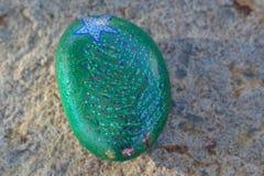 Roche peinte petit par vert avec l'arbre et l'étoile de Noël Image stock
