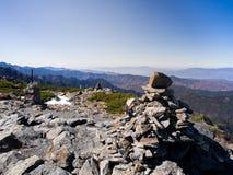 Roche, pierre et cairn sur la colline avec le fond clair de ciel bleu et de montagnes Photographie stock
