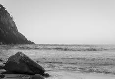 Roche sur la plage au crépuscule photo stock