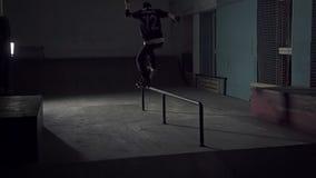 Rochen schieben unten die Geländerdocken auf einem Skateboard stock video footage