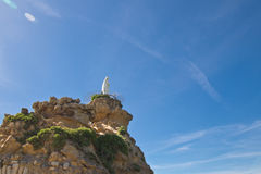 Rocher de la vierge statue of virgin mary on top of high cliff on atlantic coastline in blue sky in Biarritz, Basque country, Fran. Statue of virgin mary on top Royalty Free Stock Images