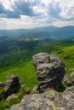 Rocher géant sur une falaise au-dessus du flanc de coteau herbeux Image stock