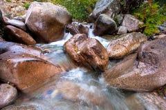Rochers énormes dans un courant de montagne images stock