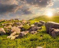 Rochers sur le pré de montagne au coucher du soleil Photos stock