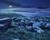 Rochers sur le pré de montagne la nuit Image stock