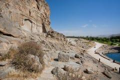 Roches au-dessus du lac et soulagements en pierre antiques dans la vallée persane avec la route rurale photos libres de droits