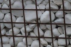 Roches blanches de décoration derrière une barrière de fer photographie stock libre de droits