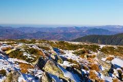 Roches bloquées par la neige et collines jaunes d'herbe et de montagne sur le fond à distance photographie stock libre de droits