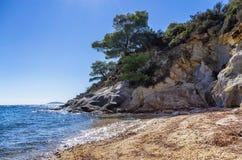 Roches dans une plage sablonneuse dans Sithonia, Chalkidiki, Grèce, avec de l'eau clair comme de l'eau de roche photo stock