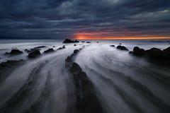 Roches de flysch en plage de Barrika au coucher du soleil Photos stock