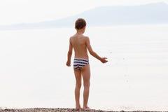Roches de lancement de garçon dans la mer Photo libre de droits