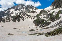 Roches de neige et un lac congelé de montagne Images stock