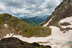 Roches de neige et un lac congelé de montagne Photographie stock libre de droits