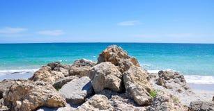 Roches de plage et eaux de turquoise Photos stock