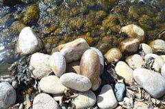 Roches de rivière dans l'eau de scintillement Photographie stock libre de droits
