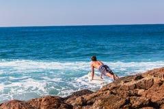 Roches de surfer sautant la mer d'entrée image libre de droits
