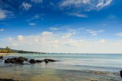 Roches en eau peu profonde transparente en des bateaux de côte à la distance Photographie stock libre de droits