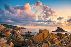Roches et bâtiments sur la mer au coucher du soleil Rivie de Livourne, Toscane photos stock