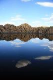 Roches et ciel se reflétant dans le lac Photos stock
