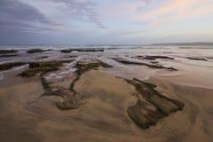Roches exposées et coucher du soleil avec de l'eau se précipitant Images libres de droits