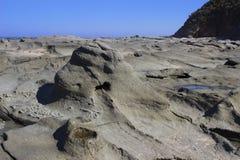 Roches grises lisses incurvées de plage Image libre de droits