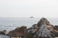 Roches, mer et petite île Photo libre de droits