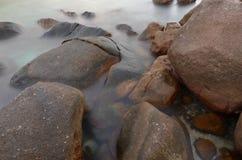 Roches rondes dans l'eau laiteuse Image stock