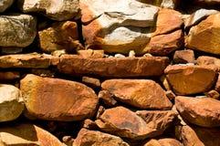 Roches rouges dans le mur aménagé en parc Image libre de droits