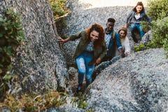 Roches s'élevantes de montagne de femme avec des amis Photos libres de droits