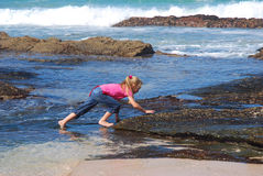 Roches s'élevantes de petite fille sur la plage Photographie stock