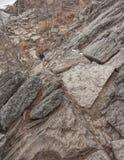 Roches s'élevantes de randonneur sur la traînée raide en hiver Photos libres de droits