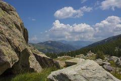 Roches sur une montagne avec l'herbe verte et une forêt verte sous un ciel nuageux bleu photos libres de droits