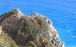 Roches, végétation et pierres antiques devant la mer Photos stock