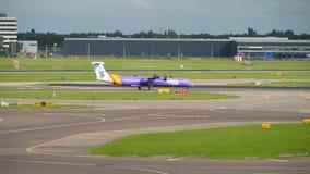 Rociada 8 Q400 del bombardero de Flybe que lleva en taxi antes de salida almacen de metraje de vídeo