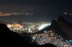 Rocinha Slum at Night and Ipanema District Behind the Mountains Stock Images
