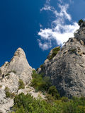 Rock against sky. Rocks with trees against blue sky Royalty Free Stock Photo