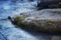 `Rock of Ages` large river boulder with flowing cold water. This 6000 x 4000 HD photo features a very large boulder with moss and fungus in a cold flowing remote stock images