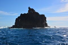 A rock amid ocean waters Stock Images