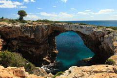 Rock arch in Cala Barques, Mallorca. Rock arch close to Cala Barques, on the east coast of Mallorca, Spanish Balearic island Royalty Free Stock Images