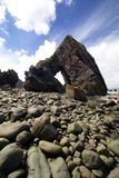 A rock arch on a beach. A Rock arch formation on stoney beach in Cornwall, England Royalty Free Stock Photography